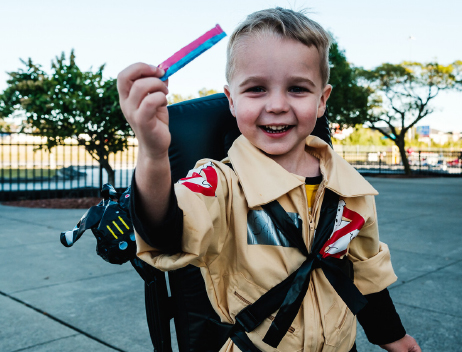 Smiling Kid in Ghostbuster Costume with Candy